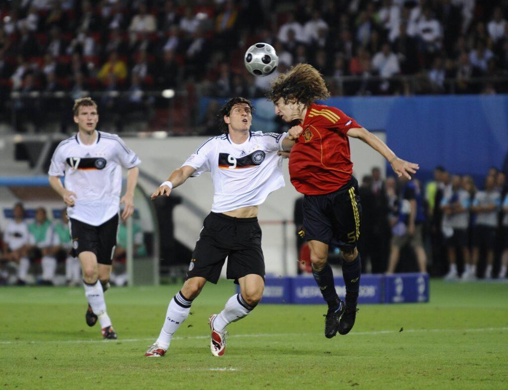 Puyol vince un duello aereo con Mario Gomez